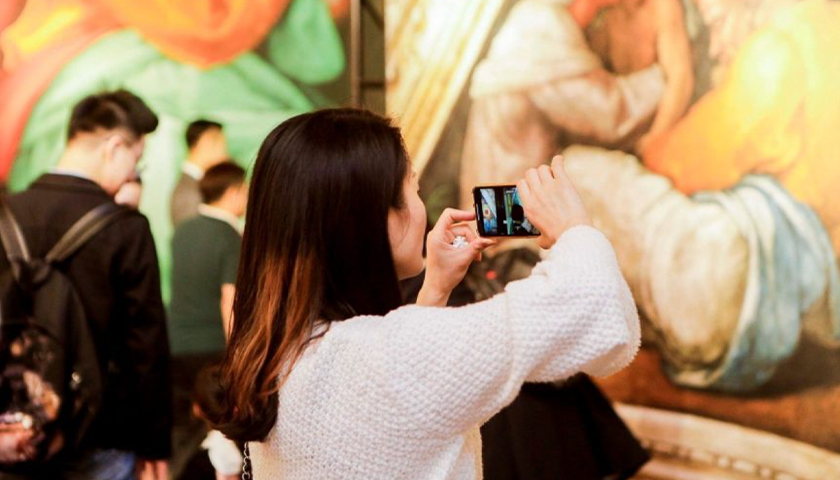 Woman using smartphone to take a photo in an art exhibit